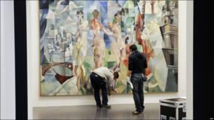 """Trabajadores colgando la pintura de Robert Delaunay """"La ville de Paris"""" (1910-1912) en el nuevo Centro Pompidou-Metz"""