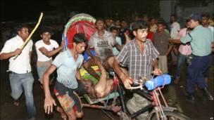 Жители Дакки везут пострадавшего в больницу