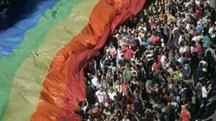Cientos de personas pasean junto a la bandera arcoiris