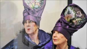 Женщина в шляпе рядом со своим портретом