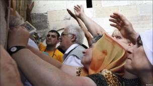 Православні прочани намагаються доторкнутися до стін монастиря