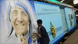 Hombre limpia una imagen de la Madre Teresa