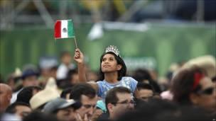 Una persona ondea una bandera de México en el Zócalo, Ciudad de México