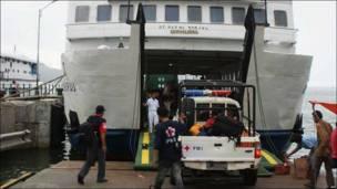 Un vehiculo de la Cruz Roja ingresa en un embarcación