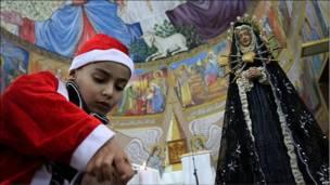 Цей палестинський хлопчик запалює свічки під час опівнічної меси в місті Ґаза.