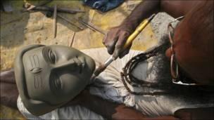 رجل هندي يصنع قناعا للأله الهندوسي شيفا استعدادا لمهرجان ديني