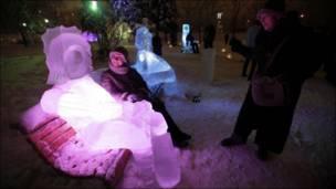 فتاة تجلس جوار تمثال تلجي في احدى الحدائق العامة في موسكو