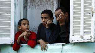 Una familia mira por la ventana de su casa en El Cairo
