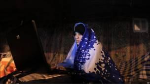Một người biểu tình dùng laptop tại lều trại trước khi cảnh sát tấn công