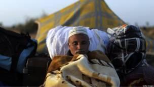 Мужчина спит в палатке для беженцев в Тунисе