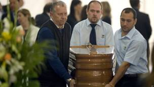 Tres personas transportan el ataúd de uno de los fallecidos en Lorca