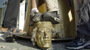 یاغي وسله وال ځواکونه په باب العزیزیه کې د قذافي مجسمه راغورځوي او د هغه د مجسمې پر سر ګرځي.