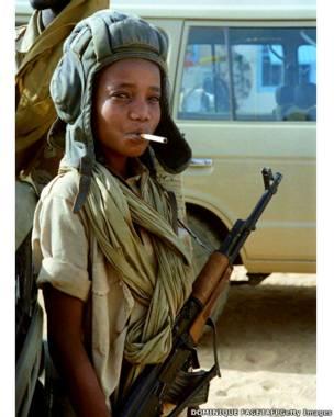 طفل يحمل بندقية كلاشينكوف