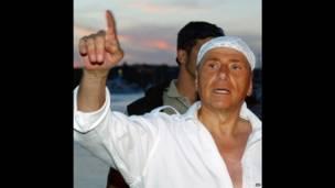 Berlusconi con un pañuelo en la cabeza
