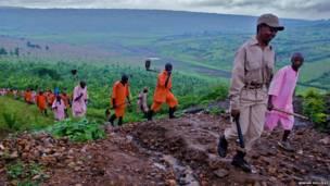 Presidiários de Nsida caminham em meio às plantações de feijão, milho e mandioca que rodeiam o centro de detenção. Foto: Graham Holliday