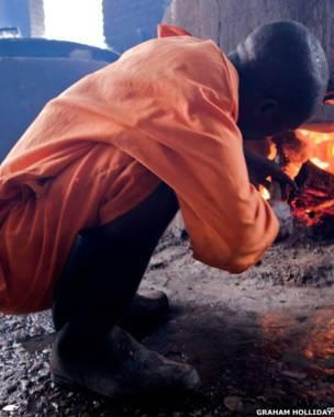 Detento de Nsinda acende fogo da cozinha que funciona à lenha. Foto: Graham Holliday