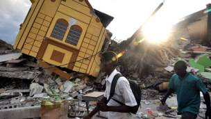 Residentes pasan por las ruinas de sus casas