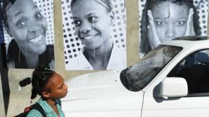 Estudiante pasa junto a afiches de haitianos