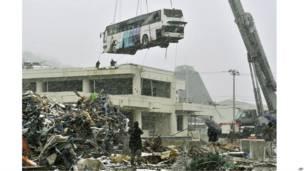Một chiếc xe buýt bị sóng quét lên đỉnh tòa nhà cao 10 mét ở Ishinomaki, Myagi được di dời