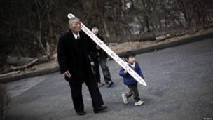 Một người ông và cháu trai đem theo bia mộ truyền thống trên đó có viết tên người thân đã mất ở