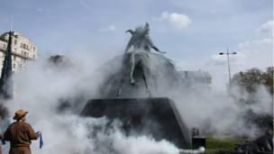 Памятник окуривают дымом.