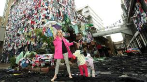 Actress Joanna Lumley stands in front of a building covered in clothes