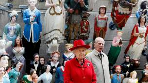 The Queen and the Duke of Edinburgh stand in front of Merchant Navy figureheads