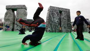 Children play on an inflatable replica of Stonehenge