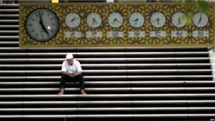 Мужчина на ступенях мечети в Куала-Лумпуре