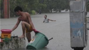Warga di tengah genangan banjir