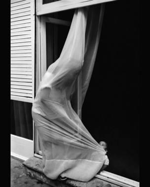 Joven mujer y niño jugando con cortina