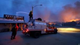 Petugas pemadam kebakaran menyemprotkan air ke sebuah restoran di kota Yarnell, AP