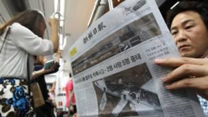 Warga Korea Selatan membaca koran yang memberitakan tentang kecelakaan pesawat Asiana di San Fransisco