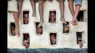 Anak-anak melihat melalui lubang-lubang di dinding Grand Gedeh, Liberia
