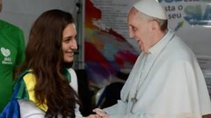 Una joven se hace una foto con una imagen de cartón del papa