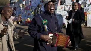 Un accordéoniste joue pour la foule réunie devant l'hôpital où Nelson Mandela est toujours hospitalisé à Prétoria. Vendredi 26 juillet 2013. Photo AP