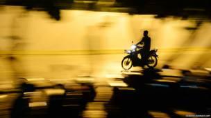 मालदीव की राजधानी माले में एक आदमी अपने मोपेड से जाता हुआ. माले की आबादी करीब 1.20 लाख है और मोपेड यहाँ बड़ा प्रचलित यातायात का साधन है.