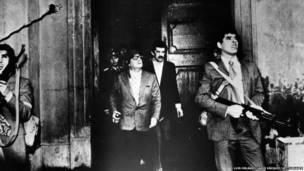 चिली में सैन्य तख्तापलट के दौरान हमलावरों की तलाश में सशस्त्र गार्ड और उनके साथ में राष्ट्रपति सल्वाडोर राष्ट्रपति भवन के एक दरवाजे के पास.