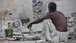 Un superviviente del terremoto toma té sentado sobre los escombros de una casa de barro que se vino abajo tras el sismo.