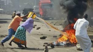 Des habitants de Mombasa essaient d'éteindre le feu mis à des pneus par de jeunes manifestants protestant contre l'assassinat d'un prédicateur radical. Vendredi 4 octobre. Photo AP