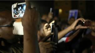 Des protestataires prenant des photos de la manifestation avec leurs téléphones portables à Khartoum. Dimanche 29 septembre 2013