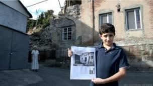 ایک لڑکا اس مسجد کی پرانی تصویر دکھا رہا ہے