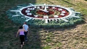 """Цветочные часы в городе Черновцы показывают 10:00, но """"солнечные часы"""" (тени от столбов и деревьев) показывают ранний вечер: если столбик переместить в центр циферблата, его тень укажет на цифру 5. Снимок сделан ровно в 17:00. Часы были созданы в 2008 году, однако уже через неделю группа нетрезвых граждан """"остановила время"""". Исправили часы ижевские мастера. Но ненадолго. В 2012 году часы снова сломались. Видимо, их судьба - показывать правильное время всего дважды в сутки. Фото: Владимир Безруков, Украина"""