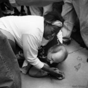 Keshia Thomas protegiendo al sujeto blanco que es atacado por la turba