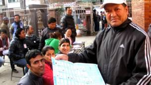 मतपत्र देखाउँदै काठमाण्डूका एक पुरुष मतदाता