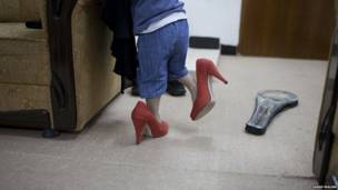 کودکی که کفش های مادرش را پوشیده. عکس از سارا مالیان