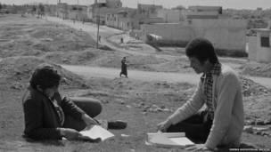 Dos estudiantes con sus libros en el campamento Baqaa