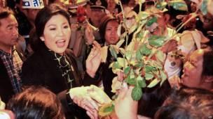 La primera ministra tailandés Yingluck Shinawatra (izquierda) recibe flores de sus partidarios al llegar al aeropuerto en la provincia de Chiang Mai, el 11 de diciembre 2013. AFP