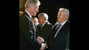 Министр иностранных дел Израиля Ариэль Шарон приветствует президента США Билла Клинтона в аэропорту Бен Гурион 12 декабря 1998 года.