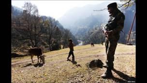 ஒரு காஷ்மீர் முஸ்லீம் சிறுமி நடந்து செல்வதை இந்தியப் படைவீரர் ஒருவர் பார்க்கிறார்
